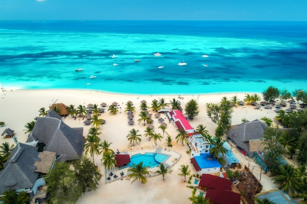 Luftaufnahme des tropischen sandstrandes mit palmen und sonnenschirmen am sonnigen tag