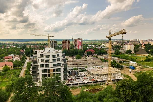 Luftaufnahme des turmhebekrans und des betonrahmens des hohen wohnungswohngebäudes im bau in einer stadt. konzept für stadtentwicklung und immobilienwachstum.