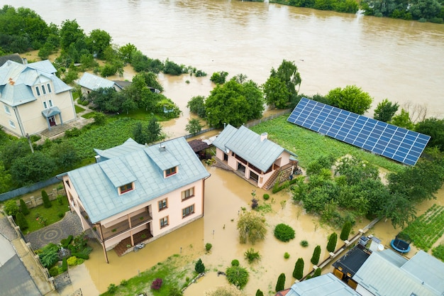 Luftaufnahme des überfluteten hauses mit schmutzigem wasser ringsum.