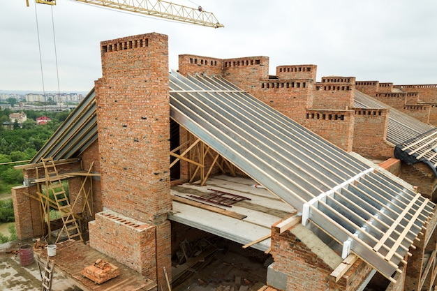 Luftaufnahme des unfertigen backsteinwohngebäudes mit der im bau befindlichen holzdachkonstruktion.