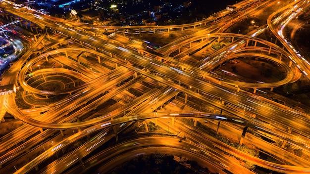 Luftaufnahme des verkehrs auf der massiven autobahnkreuzung bei nacht.