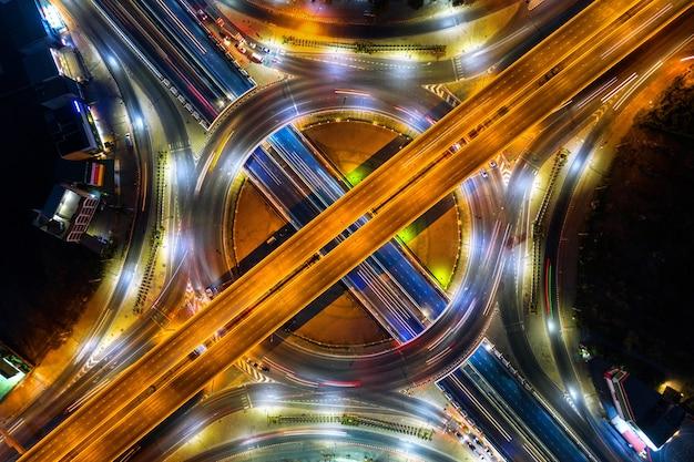 Luftaufnahme des verkehrs im kreisverkehr und auf der autobahn bei nacht