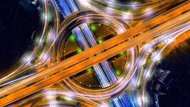 Luftaufnahme des verkehrs im kreisverkehr und auf der autobahn bei nacht.
