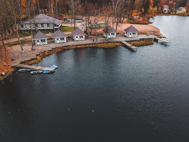 Luftaufnahme des waldes und des blauen sees. saunahaus am seeufer. holzsteg mit fischerbooten. st. petersburg, russland.