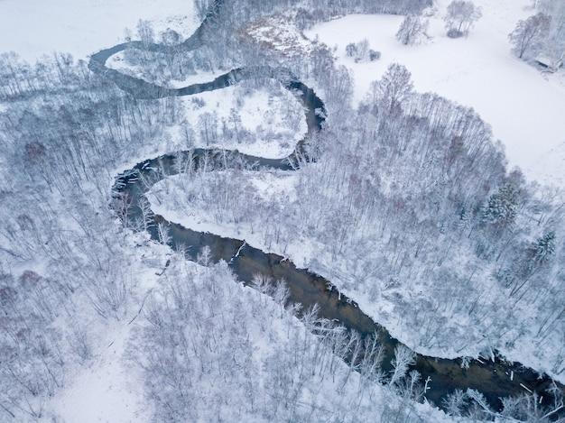 Luftaufnahme des waldflusses in der zeit des wintertages.