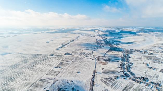 Luftaufnahme des winterlandes mit wäldern, weiße felder, im winter an einem bewölkten tag.