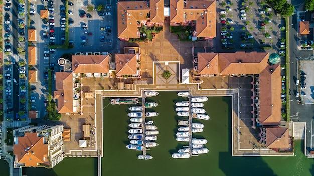 Luftaufnahme des yachthafens mit booten und yachten auf hafen des modernen wohnviertels von oben