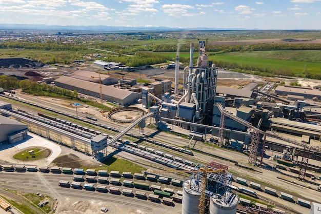 Luftaufnahme des zementwerks mit hoher betonwerksstruktur und turmdrehkran im industriellen produktionsbereich. herstellung und globales industriekonzept.