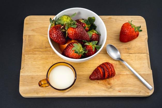 Luftaufnahme einer erdbeere geschnitten in einem holz mit einer milchbasis und einer weißen schüssel mit mehr erdbeeren