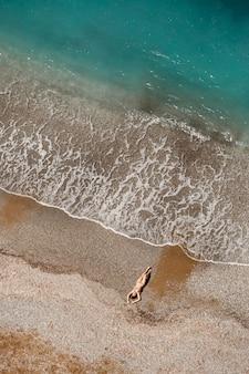 Luftaufnahme einer frau im mittelmeer in der türkei. schöne sommerlandschaft mit einem mädchen, klarem azurblauem wasser, wellen und sandstrand an einem sonnigen tag. draufsicht von einer fliegenden drohne.