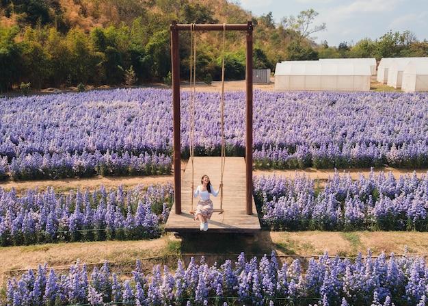 Luftaufnahme einer fröhlichen jungen asiatischen frau, die holzschaukel in margaretenblume spielt, die im garten blüht
