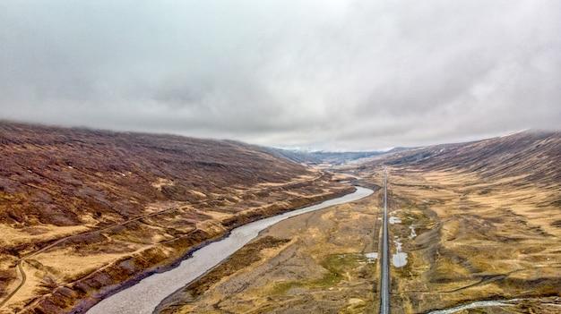 Luftaufnahme einer geraden straße in der nähe des flusses und der wasserfälle im norden islands