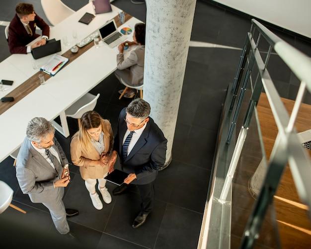 Luftaufnahme einer gruppe von geschäftsleuten, die zusammenarbeiten und ein neues projekt auf einem meeting im büro vorbereiten
