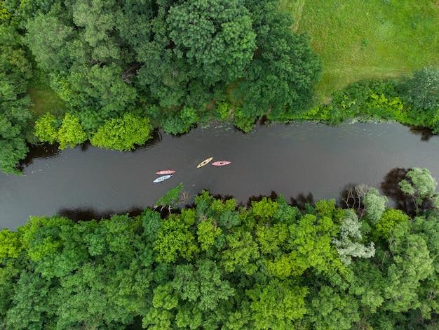 Luftaufnahme einer gruppe von kajaks, die an einem sommertag auf einem waldfluss reisen