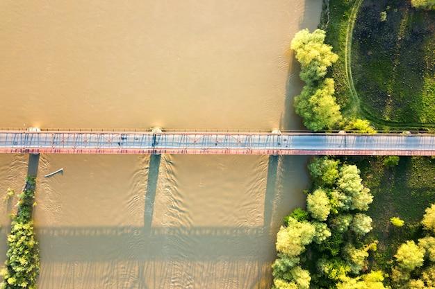 Luftaufnahme einer schmalen straßenbrücke, die sich über schlammigen breiten fluss im grünen ländlichen bereich erstreckt.