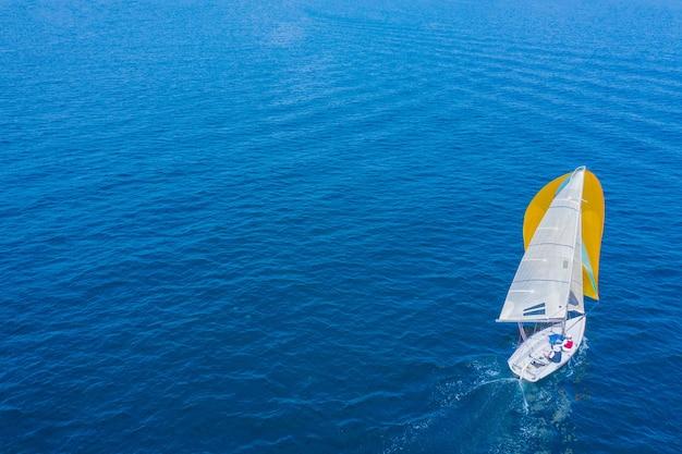 Luftaufnahme einer schönen weißen segelyacht mit einem farbigen segel.