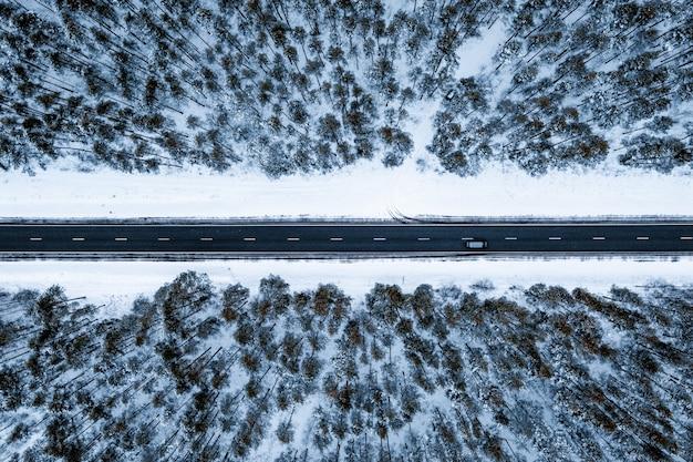 Luftaufnahme einer straße in einem wald, der im winter mit schnee bedeckt ist