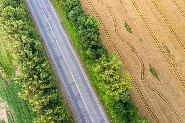 Luftaufnahme einer straße zwischen gelben weizenfeldern und grünen bäumen.