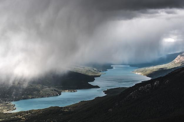 Luftaufnahme eines bewaldeten berges nahe einem fluss unter einem nebligen himmel