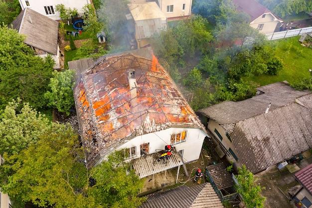 Luftaufnahme eines brennenden hauses mit orangefarbenen flammen und weißem dickem rauch.