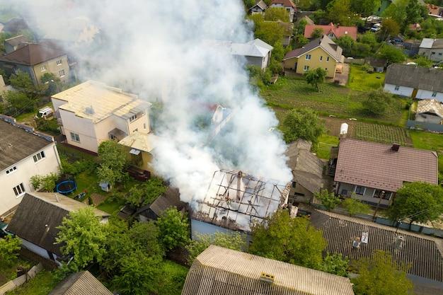 Luftaufnahme eines brennenden hauses mit orangefarbenen flammen und weißem dicken rauch.