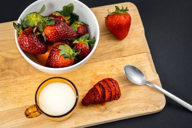 Luftaufnahme eines erdbeerschnittes auf einem holz und einer weißen schüssel mit mehr erdbeeren