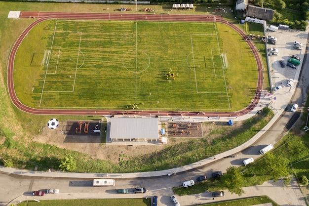 Luftaufnahme eines fußballplatzes auf einem stadion bedeckt mit grünem gras im ländlichen stadtgebiet.