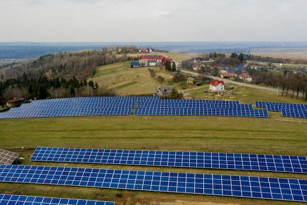 Luftaufnahme eines großen feldes eines solar-photovoltaik-panelsystems, das erneuerbare saubere energie auf grünem gras erzeugt