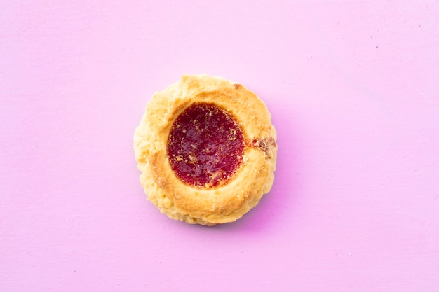 Luftaufnahme eines hausgemachten shortbread-kekses mit marmelade auf rosafarbenem hintergrund. hausgemachtes und natürliches lebensmittelkonzept. horizontale ausrichtung.