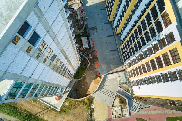 Luftaufnahme eines hohen wohnhauses mit stockwerknummern an der im bau befindlichen wand. immobilien-entwicklung.