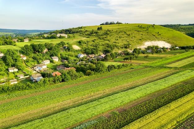 Luftaufnahme eines kleinen dorfes gewinnen viele häuser und grüne landwirtschaftliche felder im frühjahr mit frischer vegetation nach der aussaatsaison an einem warmen sonnigen tag.