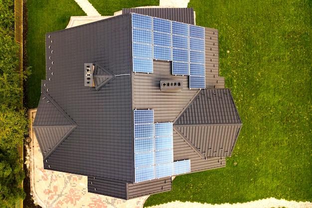 Luftaufnahme eines ländlichen privathauses mit photovoltaik-solarmodulen zur erzeugung von sauberem strom auf dem dach. autonomes wohnkonzept.
