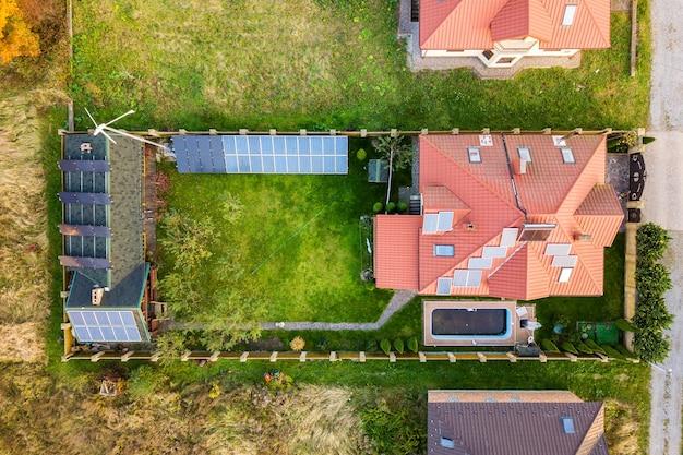 Luftaufnahme eines ländlichen privathauses mit photovoltaik-solarzellen zur erzeugung von sauberem strom auf dem dach. autonomes haus im wohngebietskonzept.