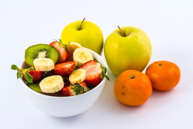 Luftaufnahme eines obstsalats, der in einer weißen schüssel auf weiß neben mandarinen und äpfeln geschnitten wird