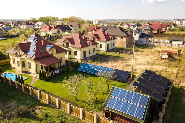 Luftaufnahme eines privathauses mit grünem grasgarten, sonnenkollektoren auf dem dach, schwimmbad mit blauem wasser und windkraftanlage.
