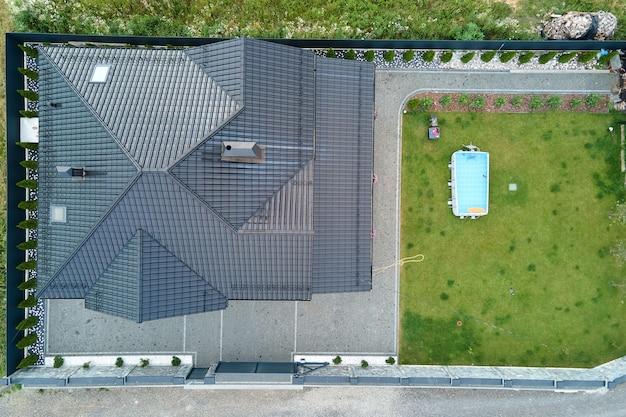 Luftaufnahme eines privathauses mit grünem hinterhof und kleinem swimmingpool auf rasen.
