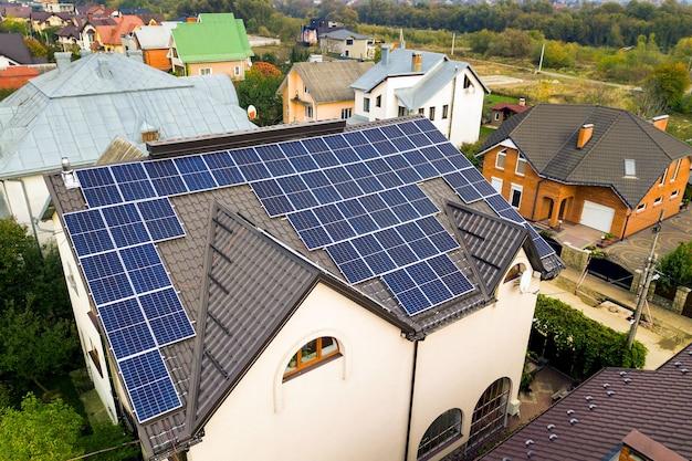 Luftaufnahme eines privathauses mit photovoltaik-solarzellen zur erzeugung von sauberem strom auf dem dach. autonomes hauskonzept.
