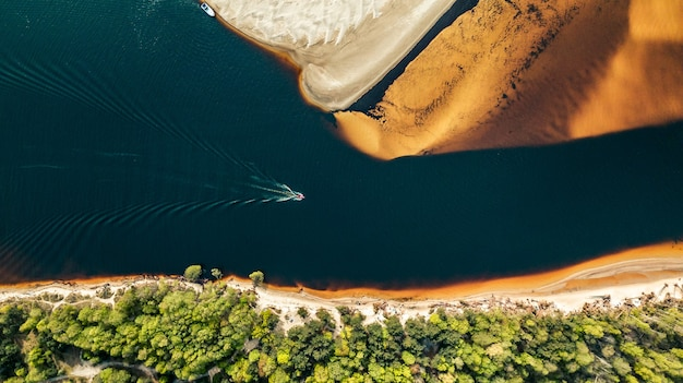 Luftaufnahme eines schnellboots, das entlang des flusses am ufer des goldenen sandes segelt