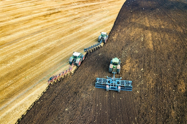 Luftaufnahme eines traktors, der schwarzes landwirtschaftliches feld nach der ernte im spätherbst pflügt