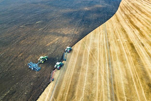 Luftaufnahme eines traktors, der schwarzes landwirtschaftliches feld nach der ernte im spätherbst pflügt.