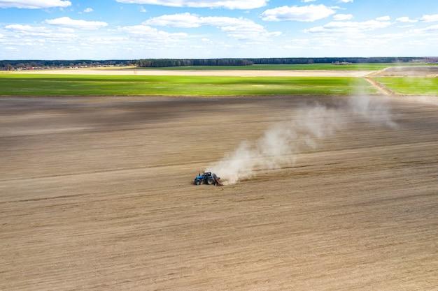 Luftaufnahme eines traktors mit montierter sämaschine, die eine direkte aussaat von feldfrüchten auf einem gepflügten landwirtschaftlichen feld durchführt. der landwirt nutzt landwirtschaftliche maschinen für den pflanzprozess, draufsicht