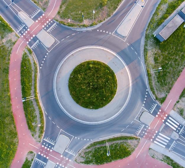 Luftaufnahme eines von grün umgebenen kreisverkehrs im sonnenlicht tagsüber