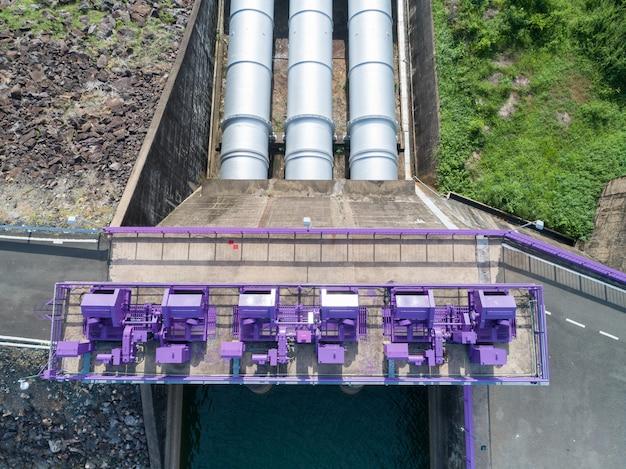 Luftaufnahme eines wasserkraftwerks und der verdammung, hydraulische sperrtür topview - konkretes wehr-stromabwärtige steigung.