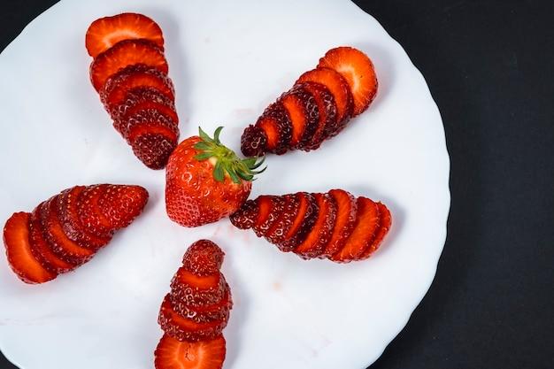 Luftaufnahme einiger geschnittener erdbeeren auf einem weißen teller auf schwarz