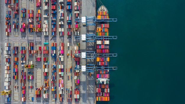 Luftaufnahme-frachtschiffanschluß, kran des frachtschiffanschlußes entladend, industriehafen der luftaufnahme mit behältern und containerschiff.