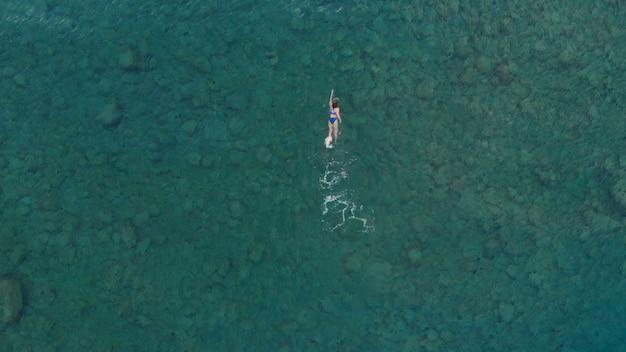 Luftaufnahme: frau, die auf oberfläche des blauen wassers schwimmt und schwimmt im transparenten mittelmeer, ansicht von oben nach unten, sommerferienkonzept