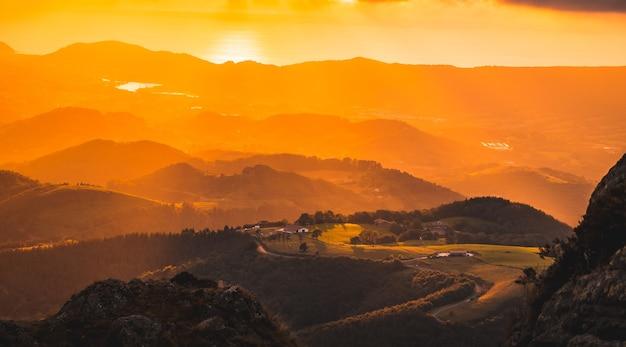 Luftaufnahme in einem gradienten der orange farben in einem schönen sonnenuntergang von einer spitze eines berges