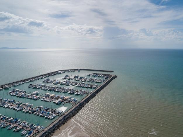 Luftaufnahme über hafen mit luxusyachten - segelboothafen, viele schönen festgemachten segeljachten im seehafen mit wolken des blauen himmels.