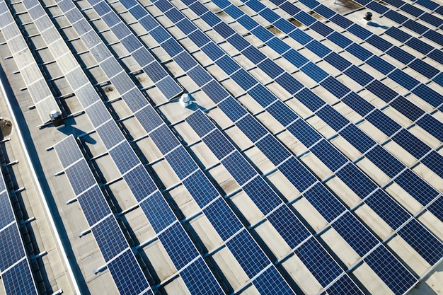 Luftaufnahme vieler photovoltaik-solarmodule, die vom dach des industriegebäudes montiert werden.