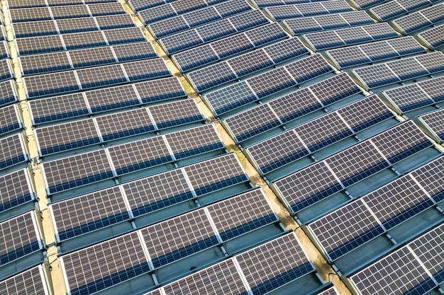 Luftaufnahme vieler photovoltaik-sonnenkollektoren, die vom industriegebäudedach montiert werden.